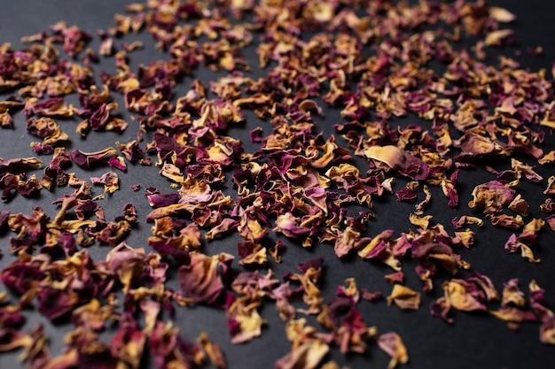 Studio fotografico di foglie essiccate di rosa tea, sul tavolo nero.