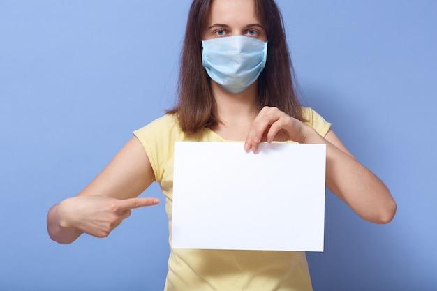 Foto dello studio di bella giovane donna carismatica che tiene foglio di carta in bianco, facendo gesto, mostrando direzione, esaminando direttamente la macchina fotografica, essendo nella maschera dal coronavirus. concetto di sicurezza.