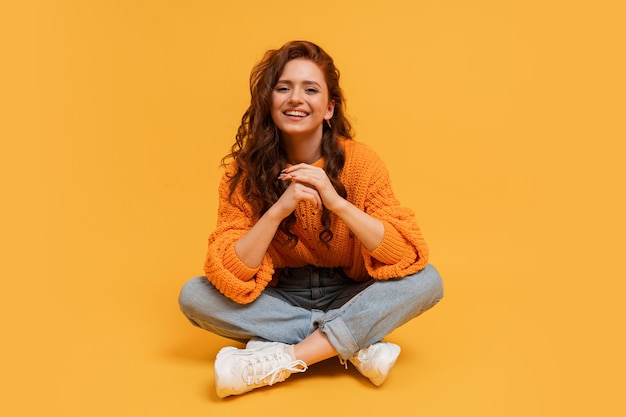 Foto in studio di una bella ragazza dai capelli rossi hipster in elegante autfit autunnale in posa su un muro giallo