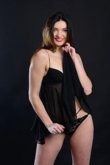 Foto in studio di una donna seducente in una lingerie nera sullo sfondo dello studio