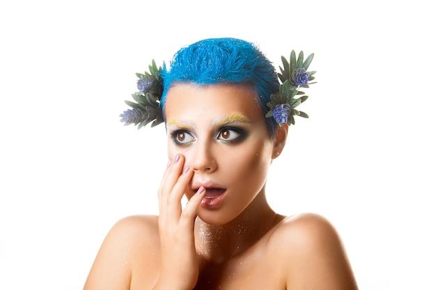 La foto dello studio ha sorpreso la ragazza con i fiori tra i capelli e il trucco multicolore isolato