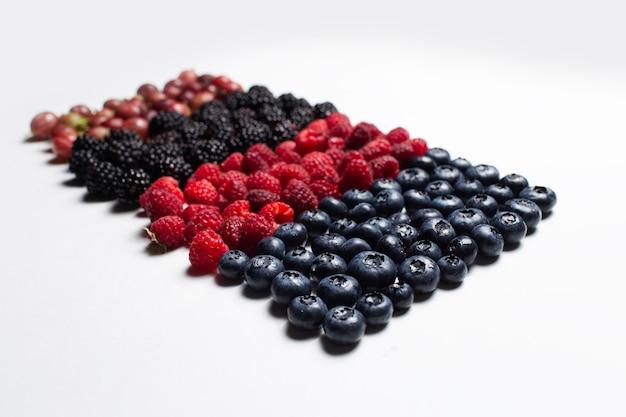 Studio immagine di frutti di bosco freschi situati in linea, sul tavolo bianco.