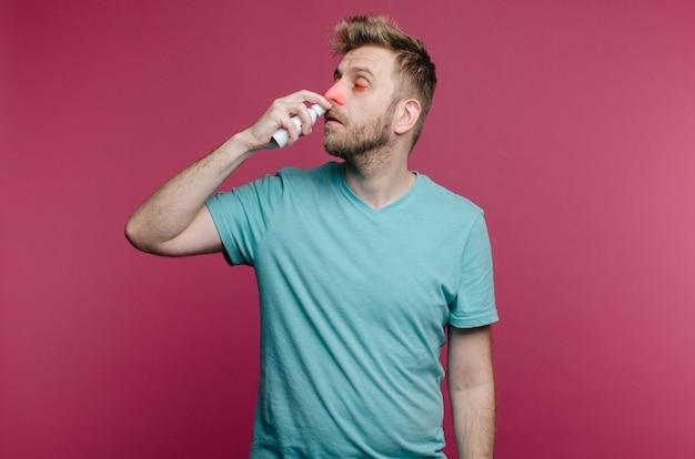 L'immagine dello studio da un giovane usa lo spray per il naso. il ragazzo malato isolato ha il naso che cola