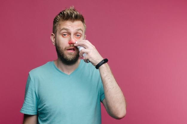 L'immagine dello studio da un giovane usa lo spray per il naso