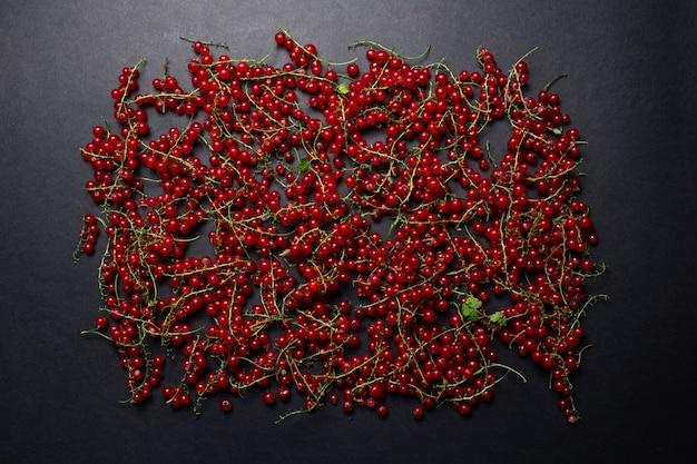 Studio immagine di ribes rosso sparsi su uno sfondo scuro.