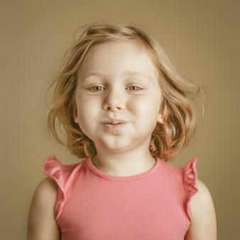 Ritratto in studio di una bambina di 5 anni con espressione divertente.