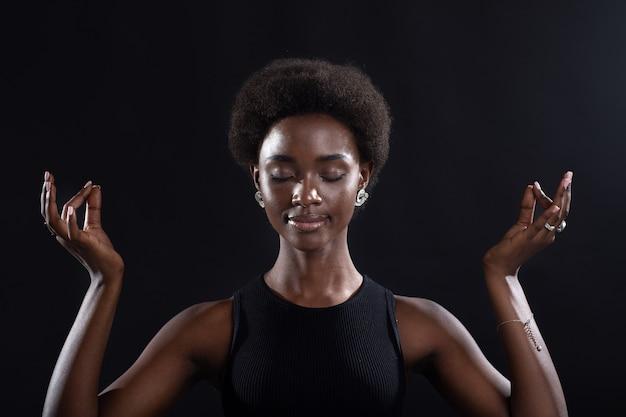 Ritratto in studio di modello femminile afroamericano che mostra mudra yoga zen o gesto di segno ok. pace interiore, salute e meditazione della donna