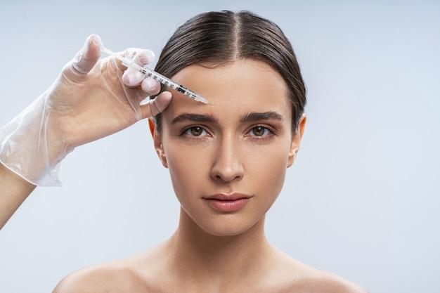 Ritratto in studio di giovane donna attraente che riempie le iniezioni facciali di bellezza nel centro di bellezza