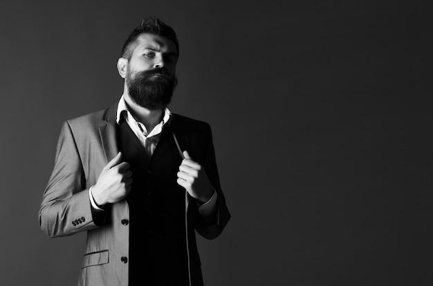 Ritratto in studio di un uomo barbuto hipster. barba e baffi maschili. bell'uomo barbuto alla moda. uomo barbuto in giacca e cravatta. bellezza maschile, moda. maschio sexy, macho, barba lunga. bianco e nero.