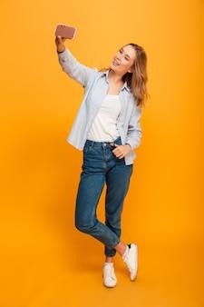 Ritratto dello studio di bella donna che sorride e che prende selfie che si fotografa, isolato sopra spazio giallo