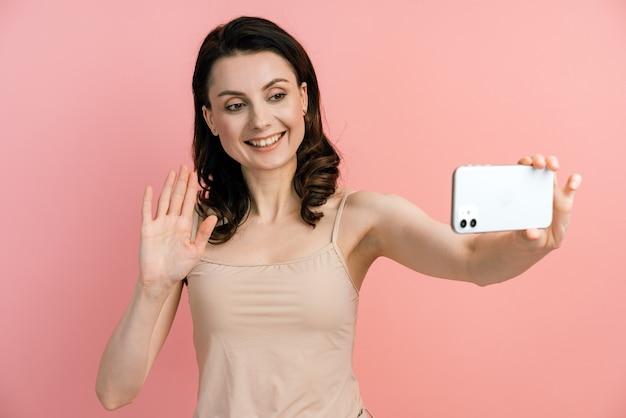 Ritratto in studio di bella donna sorridente e tenendo selfie