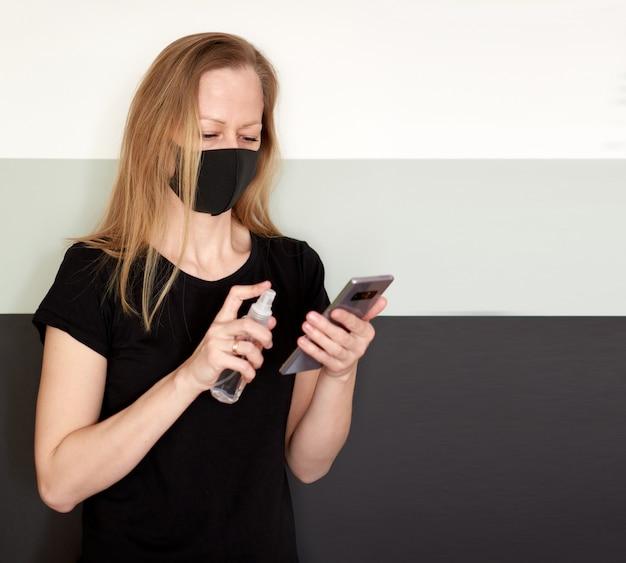 Ritratto in studio di donna bionda in maschera per il viso che disinfetta il telefono con disinfettante spray durante il coronavirus