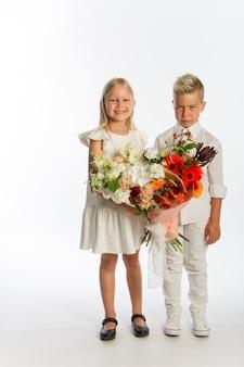 Ritratto in studio ragazzo dà ragazza bouquet festivo, concetto di congratulazioni,