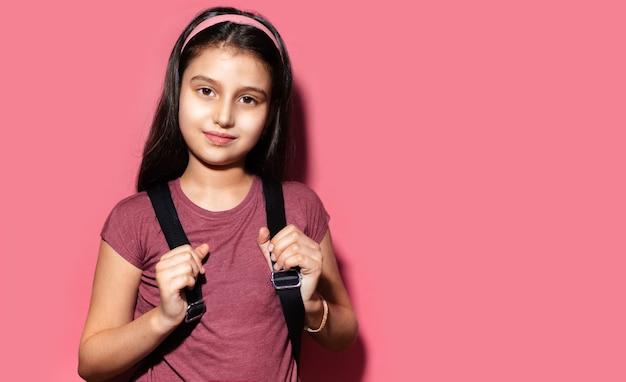 Ritratto dello studio della ragazza castana del bambino che si prepara per la scuola, zaino da portare e fascia su fondo di colore rosa pastello con lo spazio della copia.