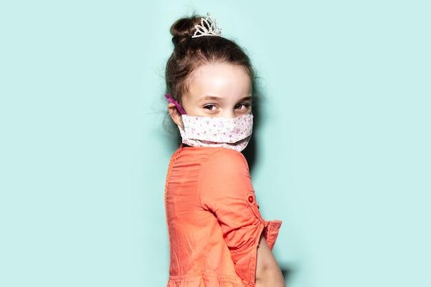 Ritratto in studio di bambina che indossa maschera protettiva medica sul viso contro il coronavirus