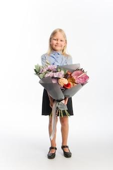 Ritratto in studio di ragazza bionda carina in uniforme scolastica con bouquet regalo bellissimo, fuoco selettivo