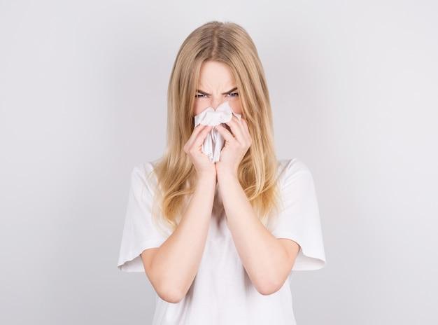Ritratto in studio di donna caucasica malsana carina con un tovagliolo di carta starnuti a causa di allergia