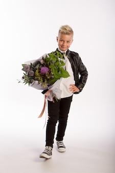 Ritratto dello studio del ragazzo caucasico biondo alla moda con il mazzo del regalo, muro bianco, spazio della copia
