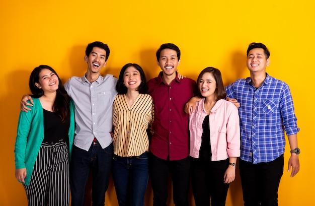 Ritratto dello studio del gruppo di giovani amici asiatici che esaminano macchina fotografica