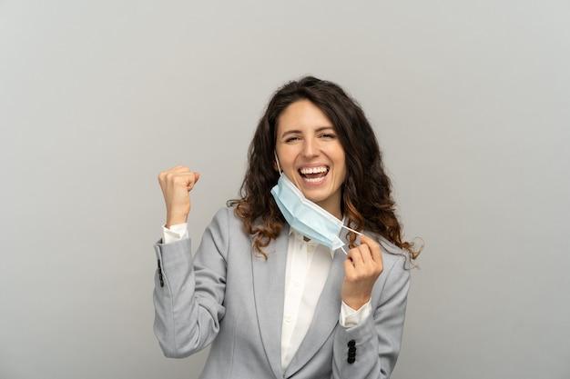 Ritratto in studio di donna d'affari felice che toglie la maschera dal viso, alzando il pugno su sfondo grigio.