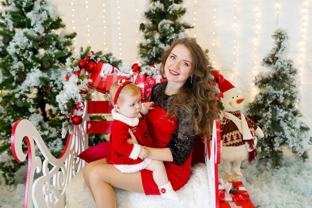 Ritratto in studio di felice madre e figlia in panni di babbo natale seduto vicino all'albero di natale