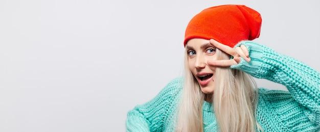Ritratto dello studio di giovane ragazza bionda felice che mostra il segno di pace su fondo bianco. indossa un cappello arancione e un maglione blu.