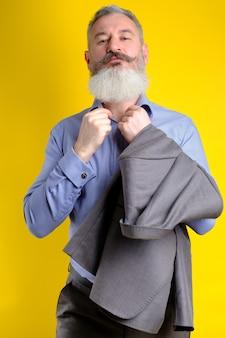 Ritratto in studio uomo bello barbuto maturo in tailleur grigio che guarda alla fotocamera, stile di vita di professione di lavoro, sfondo giallo.