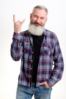 Ritratto in studio di uomo barbuto maturo in abiti casual che mostra le corna sul gesto