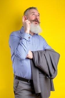 Ritratto in studio uomo barbuto maturo vestito in tailleur grigio guarda pensieroso da parte, pensa a qualcosa, sfondo giallo