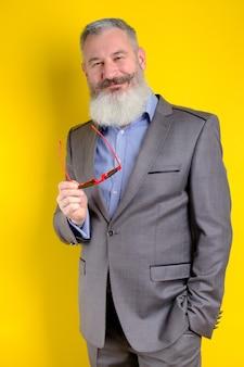 Ritratto in studio uomo barbuto maturo in tailleur grigio che guarda alla fotocamera, stile di vita di professione di lavoro, sfondo giallo.