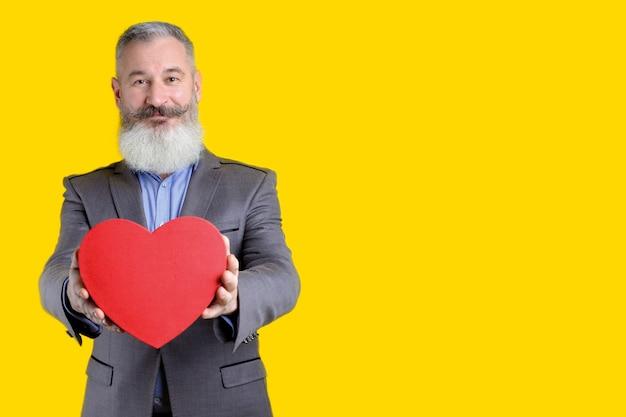 Ritratto dello studio dell'uomo barbuto maturo che tiene fuori il contenitore di regalo di forma del cuore, fondo giallo, spazio della copia