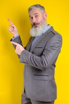 Ritratto in studio maturo uomo d'affari vestito in abito grigio punti da parte, ti scelgo questo, sfondo giallo