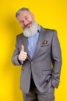Ritratto in studio maturo uomo d'affari vestito in abito grigio mostra pollice in alto, concetto di business di successo, sfondo giallo