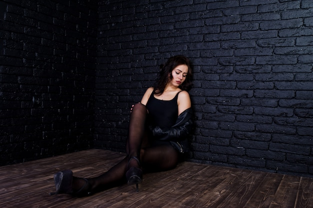 Ritratto dello studio della ragazza sexy del brunette in bomber nero contro il muro di mattoni.