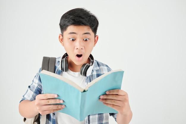 Ritratto dello studio dello scolaro eccitato scioccato con lo zaino che legge il testo nel libro