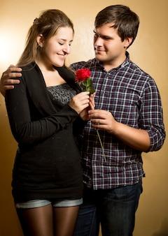 Ritratto in studio di un uomo sorridente che dà una rosa rossa alla ragazza carina
