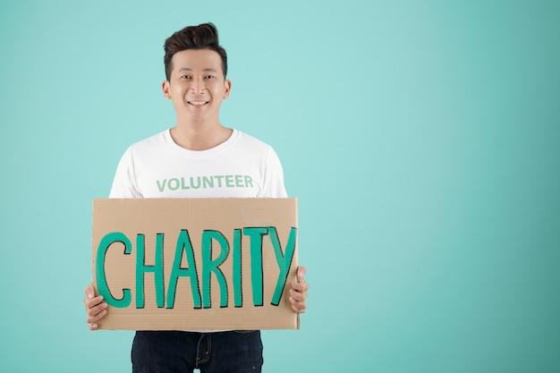 Ritratto in studio di un giovane volontario di fondazione di beneficenza sorridente che tiene in mano un grande cartellone