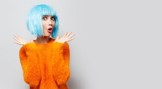 Ritratto in studio di ragazza sorpresa con parrucca blu, isolata sul muro grigio.