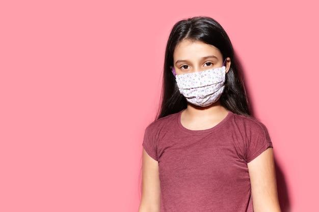 Ritratto in studio di una ragazza adolescente che indossa una maschera medica contro il coronavirus