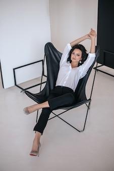 Ritratto in studio di una donna in posa su una sedia