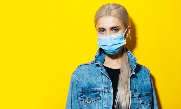 Ritratto in studio di giovane ragazza bionda in giacca di jeans, che indossa una maschera medica contro il coronavirus su giallo con copia spazio.