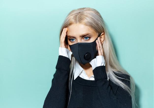 Ritratto dello studio di giovane ragazza bionda che ha mal di testa indossando maschera medica nera sul ciano
