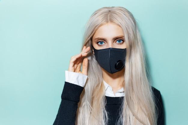 Ritratto in studio di giovane ragazza bionda che indossa una maschera respiratoria nera contro il coronavirus sul colore dell'acqua.