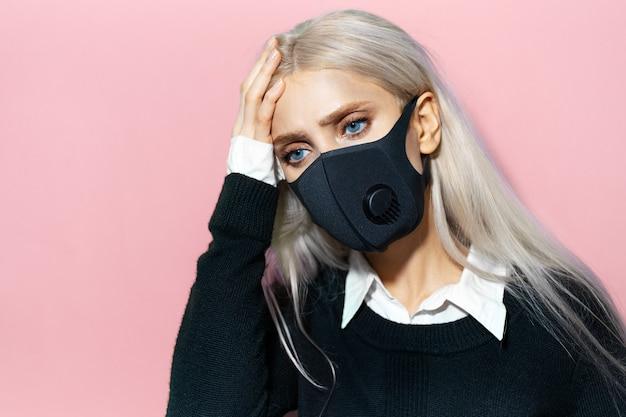 Ritratto in studio di una giovane ragazza bionda che indossa una maschera respiratoria nera sul viso contro il coronavirus, tenendo la mano sulla testa a causa del dolore. sfondo di colore rosa pastello.