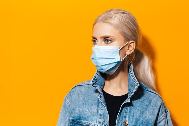 Ritratto in studio di una giovane ragazza bionda che indossa una maschera medica contro il coronavirus su sfondo di colore arancione.