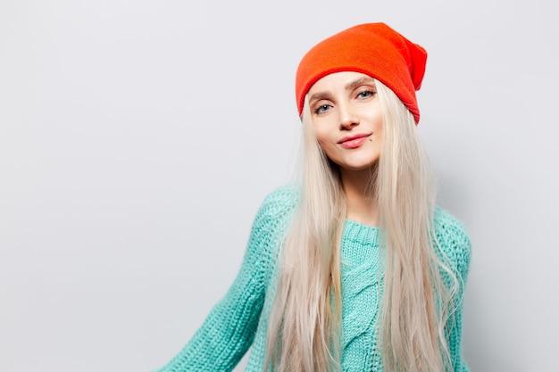 Ritratto in studio di giovane ragazza bionda che indossa cappello arancione e maglione blu su sfondo bianco.