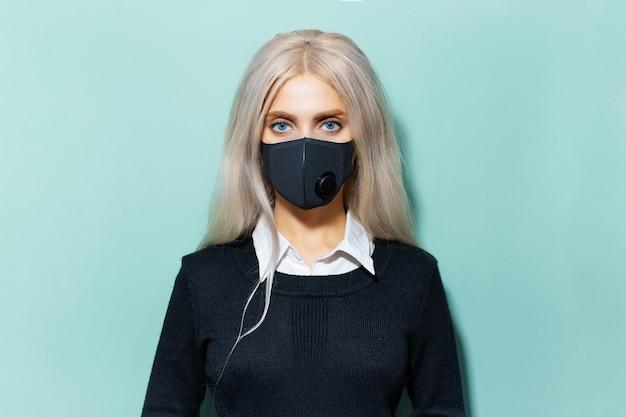 Ritratto in studio di giovane ragazza bionda con gli occhi azzurri in forma scolastica, che indossa una maschera respiratoria nera contro il coronavirus su sfondo di ciano, colore acqua menthe.