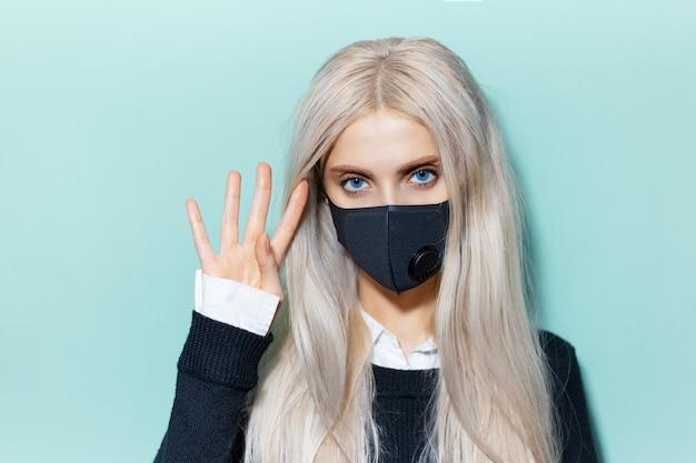 Ritratto in studio di giovane ragazza bionda con gli occhi azzurri, che indossa una maschera respiratoria di colore nero, contro il virus. sfondo di colore ciano, aqua menthe.