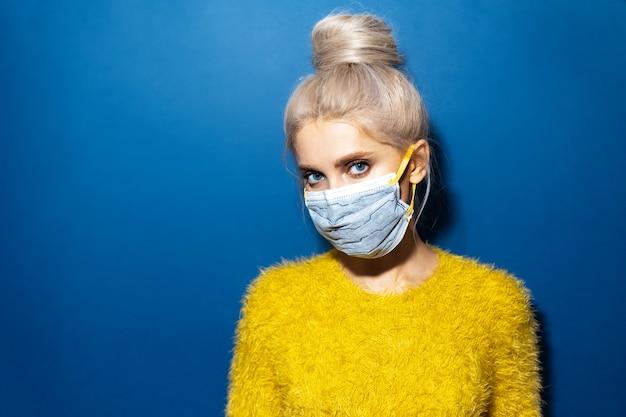 Ritratto in studio di giovane ragazza bionda con chignon per capelli che indossa maschera di sicurezza respiratoria medica sul viso contro il coronavirus sul blu