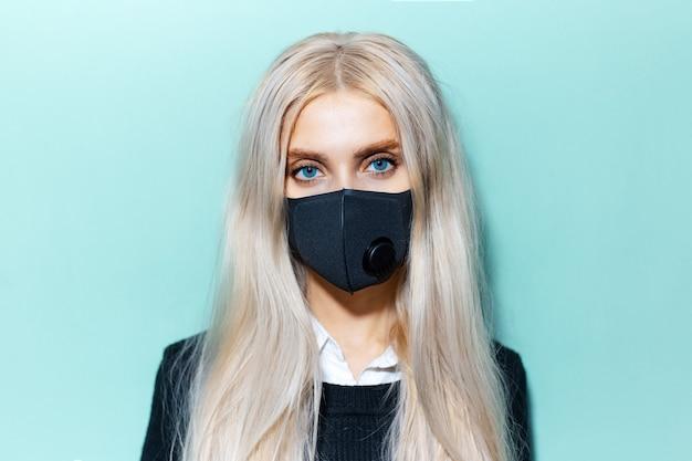 Studio ritratto di giovane donna bionda con gli occhi azzurri che indossa la maschera medica nera sulla superficie di colore ciano